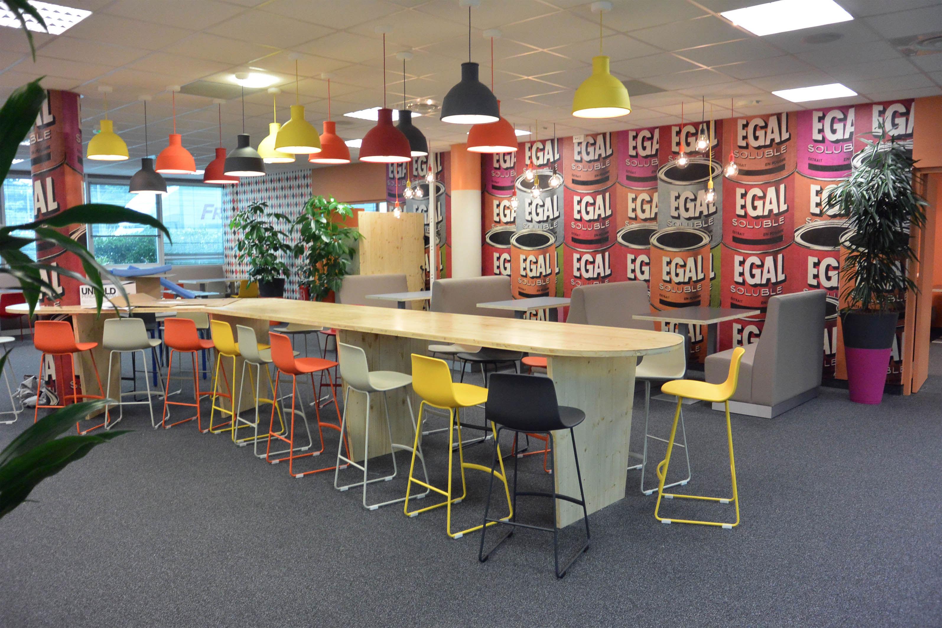 Des espaces différenciés et colorés : banquettes, manges debouts et tabourets design