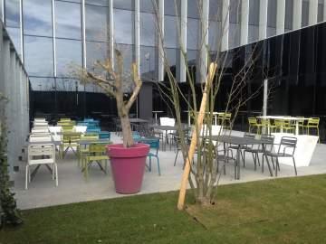 Un extérieur design : chaises et tables tout en métal de plusieurs couleurs pour apporter de la gaîté