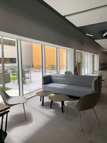 Coin lounge avec un joli canapé, deux tables basses et des chauffeuses design