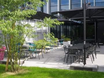 Quelques parasols, des chaises et tables en métal et en couleur, un extérieur qui a du style