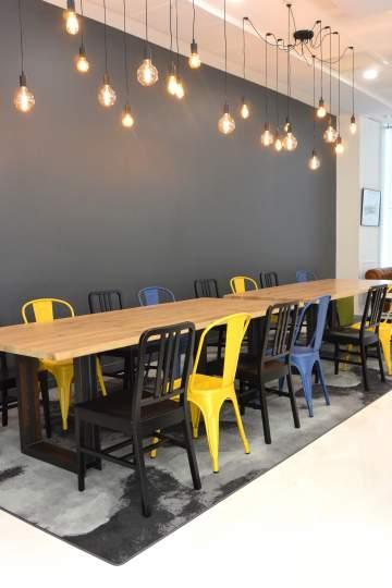 Superbe tablée colorée : belle table en bois brut, chaises alu et métal coloré associés à des luminaires modernes