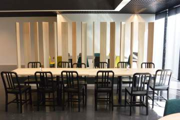 Grande tablée pour ce restaurant : table dans un joli bois assorti de chaises en alu pour un look moderne et épuré